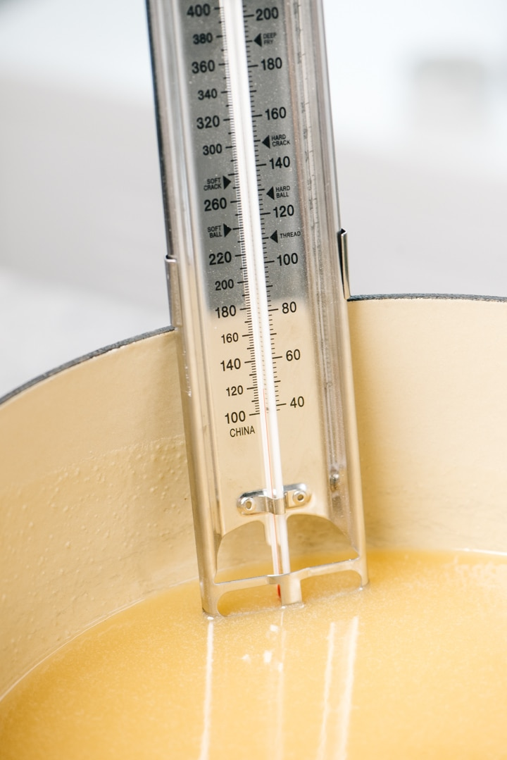 A candy thermometer inserted into caramel candy mixture in a dutch oven.