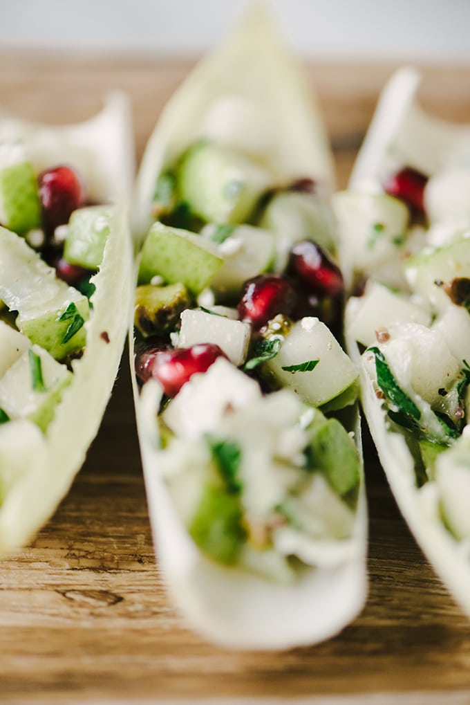 A detail image of endive leaves stuffed pear, pomegranate, and blue cheese - these are a fast and easy cocktail party appetizer!