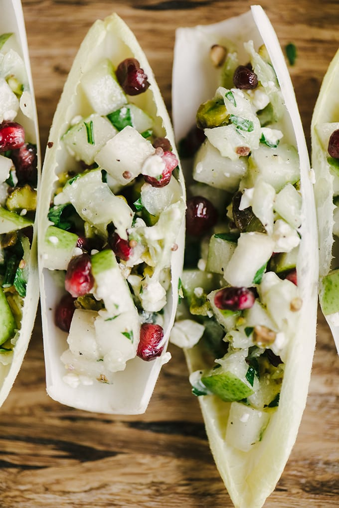 A close-up image of healthy endive appetizer cups stuffed with pear, pomegranate, and blue cheese.