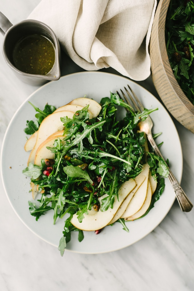Arugula pear salad with pomegranates and pistachios on a blue plate with a silver fork a small pitcher of champagne mustard vinaigrette.
