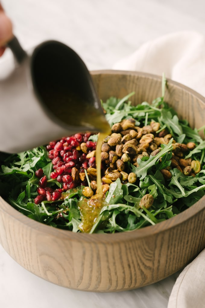 A woman's hand pouring a pitcher of vinaigrette over an arugula pear salad with pomegranates and pistachios.