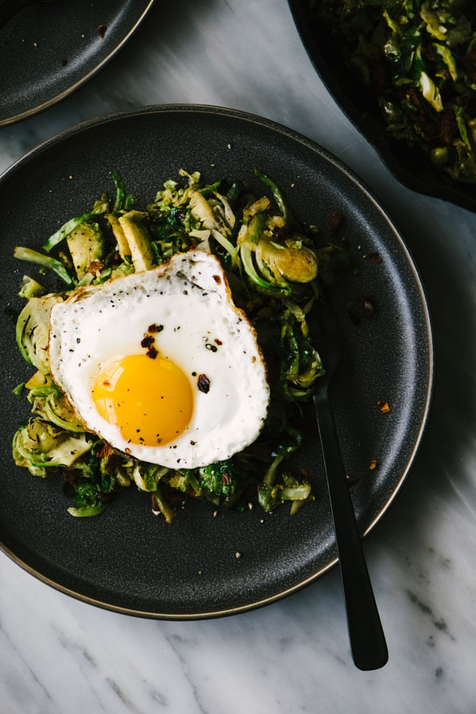 A plate of Whole30 brussels sprouts breakfast hash with bacon and a fried egg.