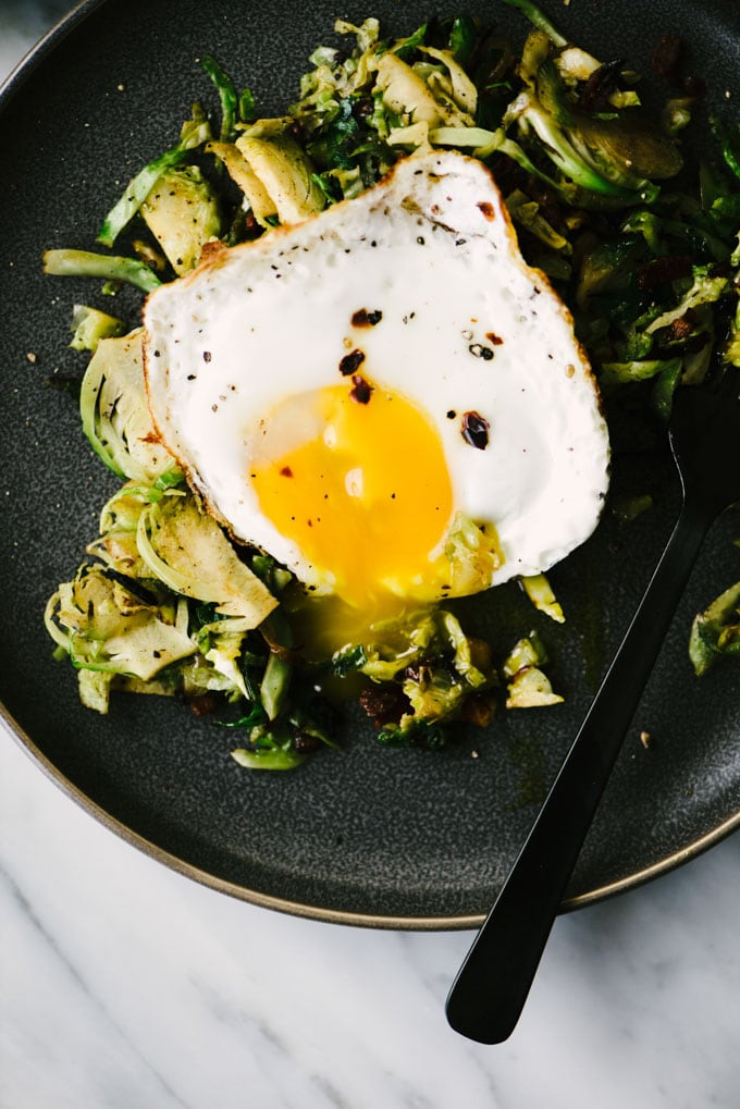 A plate of brussels sprouts hash with bacon and a runny fried egg.