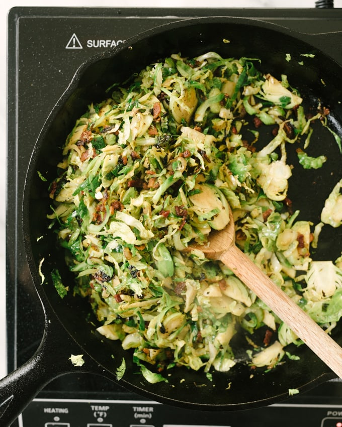 Brussels sprouts hash with bacon in a cast iron skillet.