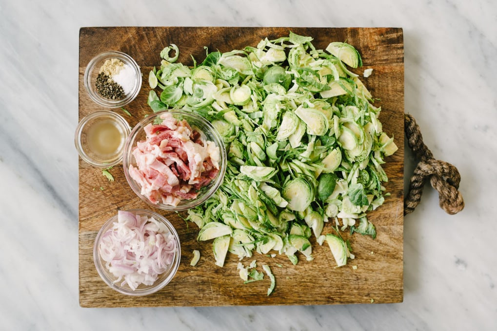 The ingredients for brussels sprouts hash on a wood cutting board - shaved brussels sprouts, chopped bacon, sliced shallots, cider vinegar, and seasoning.