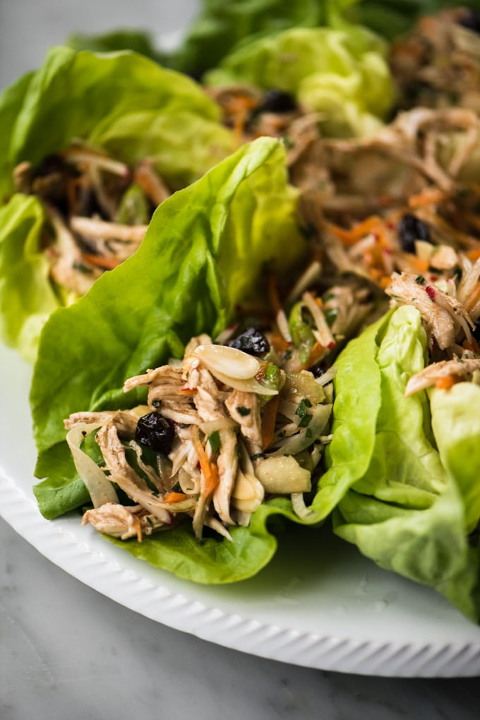 A close-up image of whole30 chicken salad wraps with dried cherries, almonds, and raw vegetables resting on a white platter.