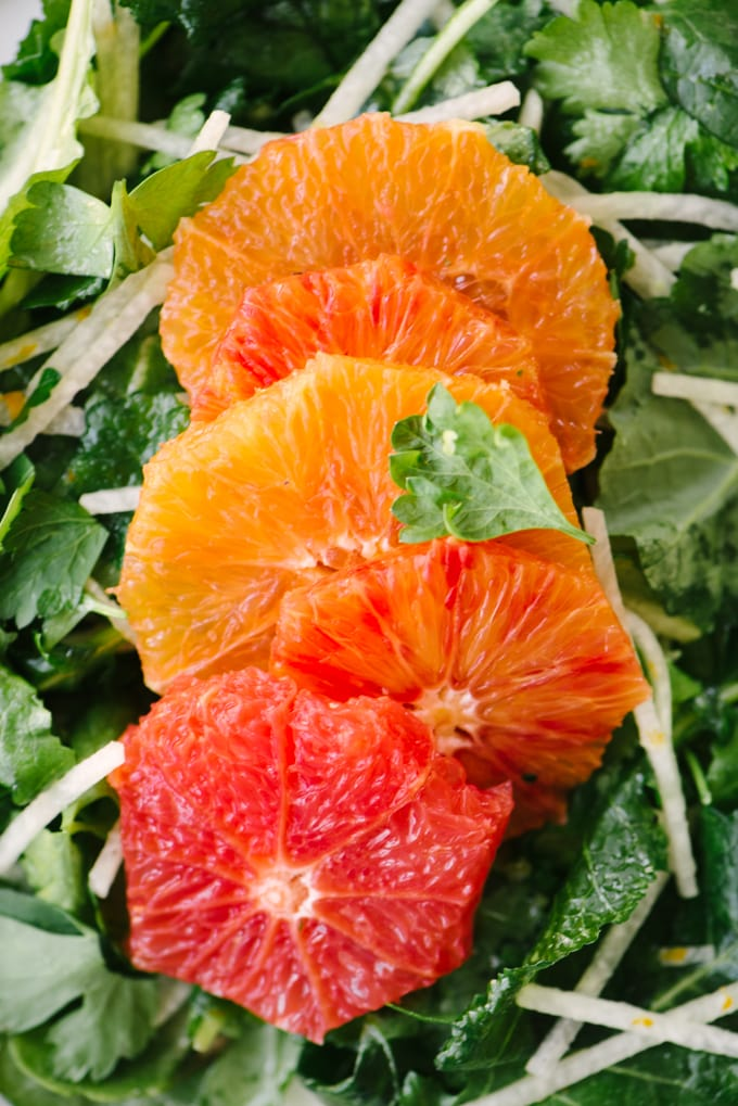 A close-up detail of citrus slices on a bed of kale tossed with jicama and Whole30 vinaigrette.