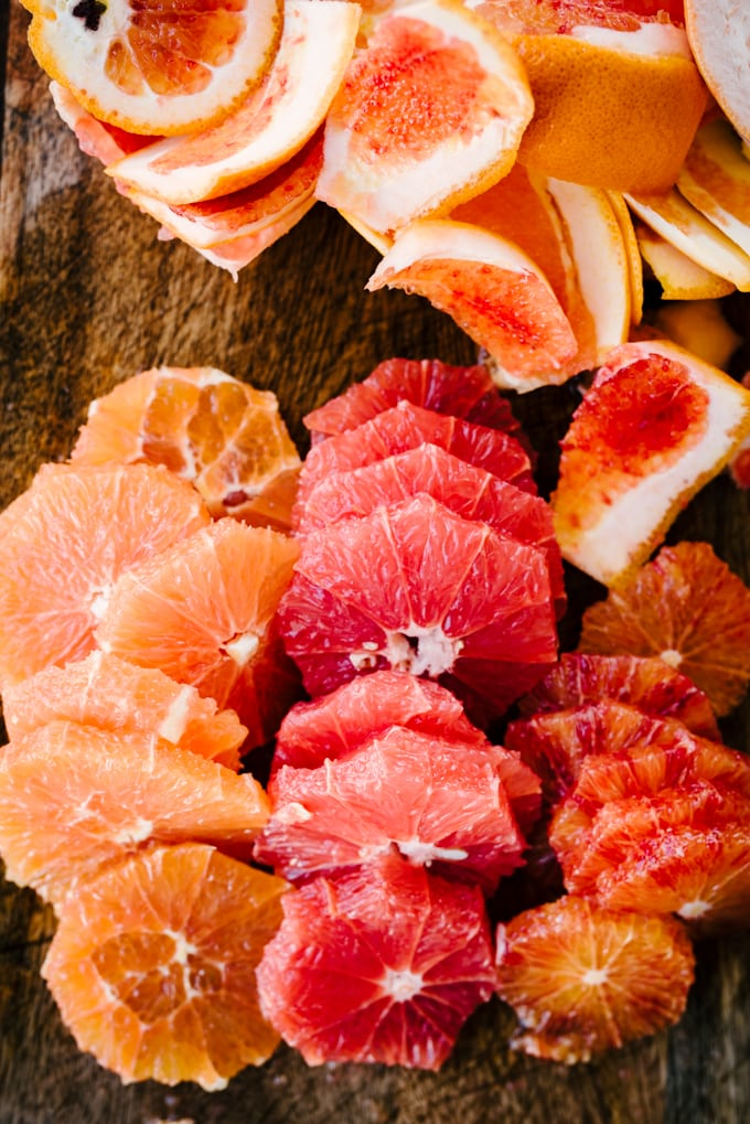 Slices of orange and grapefruit on a cutting board with citrus peels in the background.