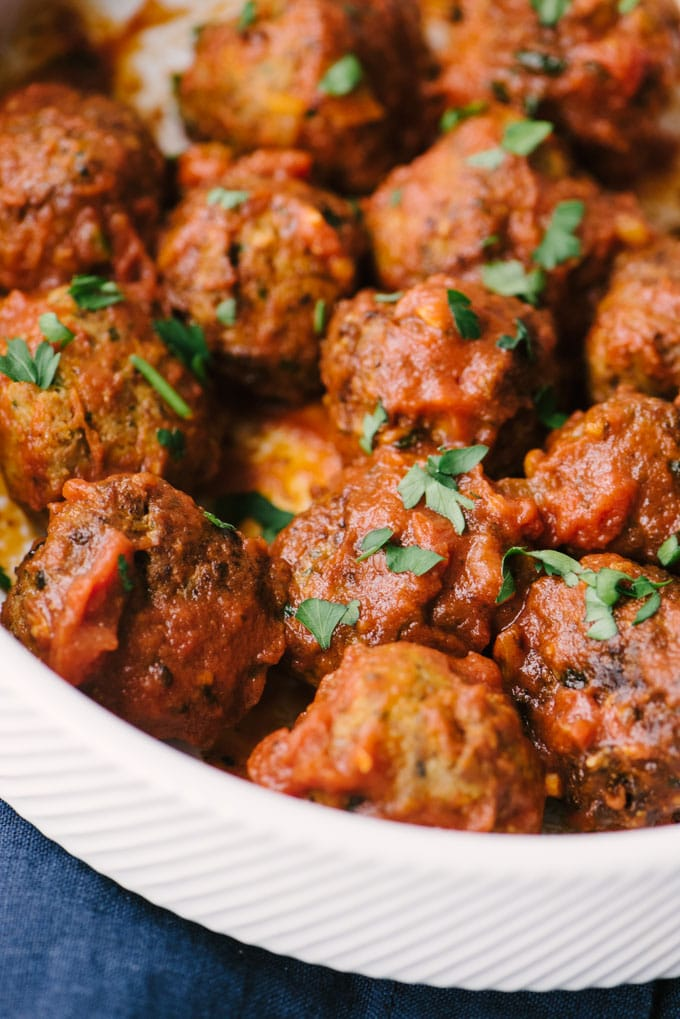 A close-up image of flavor packed paleo turkey meatballs tossed with whole30 marinara sauce in a white bowl with a blue napkin.
