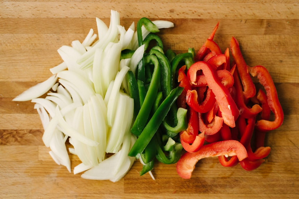 How to make a paleo burrito bowl. Sliced onions, green bell peppers, and red bell peppers on a wooden cutting board.
