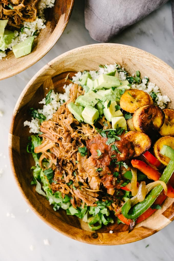 An overhead view of a paleo burrito bowl! A wooden bowl layered with cilantro lime cauliflower rice, romaine lettuce, sautéed onions and peppers, pulled pork, fried plantains and diced avocado.