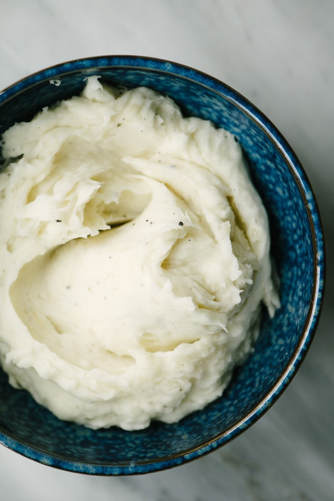 Paleo and whole30 mashed yucca root in a blue bowl on a marble table.