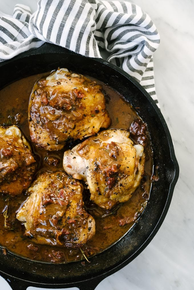Crispy sun dried tomato chicken in a cast iron skillet with a grey and white striped napkin on a marble background.