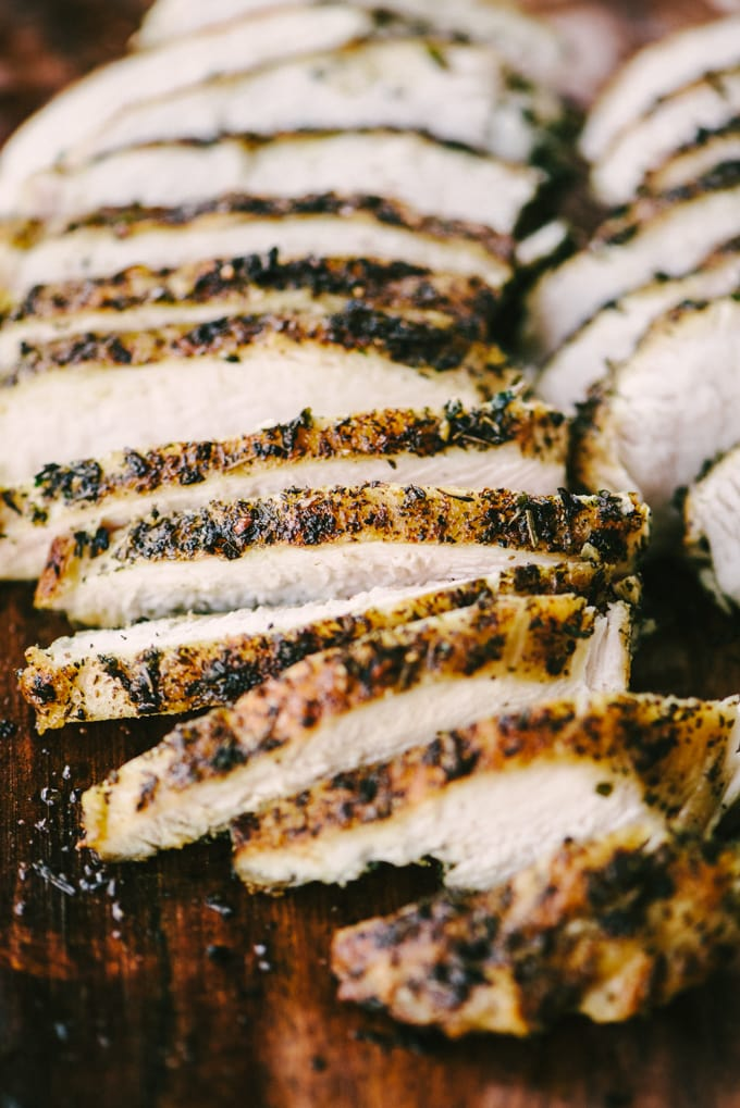 Pan seared italian-seasoned chicken breasts thinly sliced on a cutting board for preparing a Whole30 BLT chicken salad.