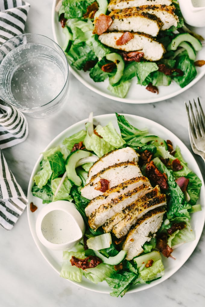 Two plates of whole30 BLT chicken salads with ranch dressing on a marble table with a glass of sparkling water.