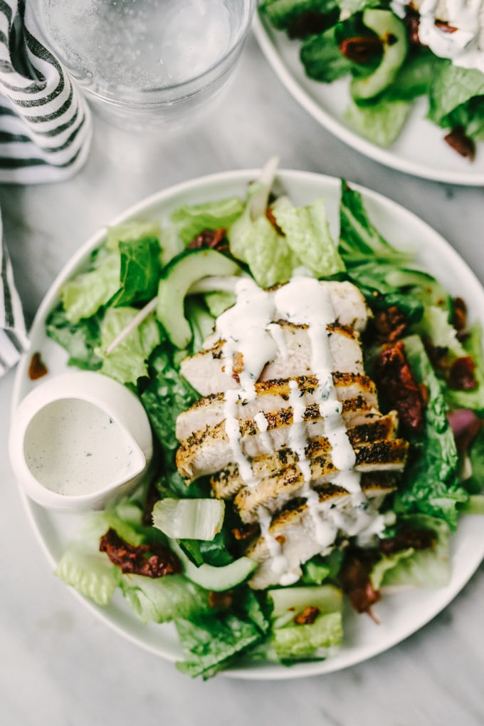 A BLT chicken salad with Whole30 ranch dressing on marble table with a glass of water and a striped napkin.