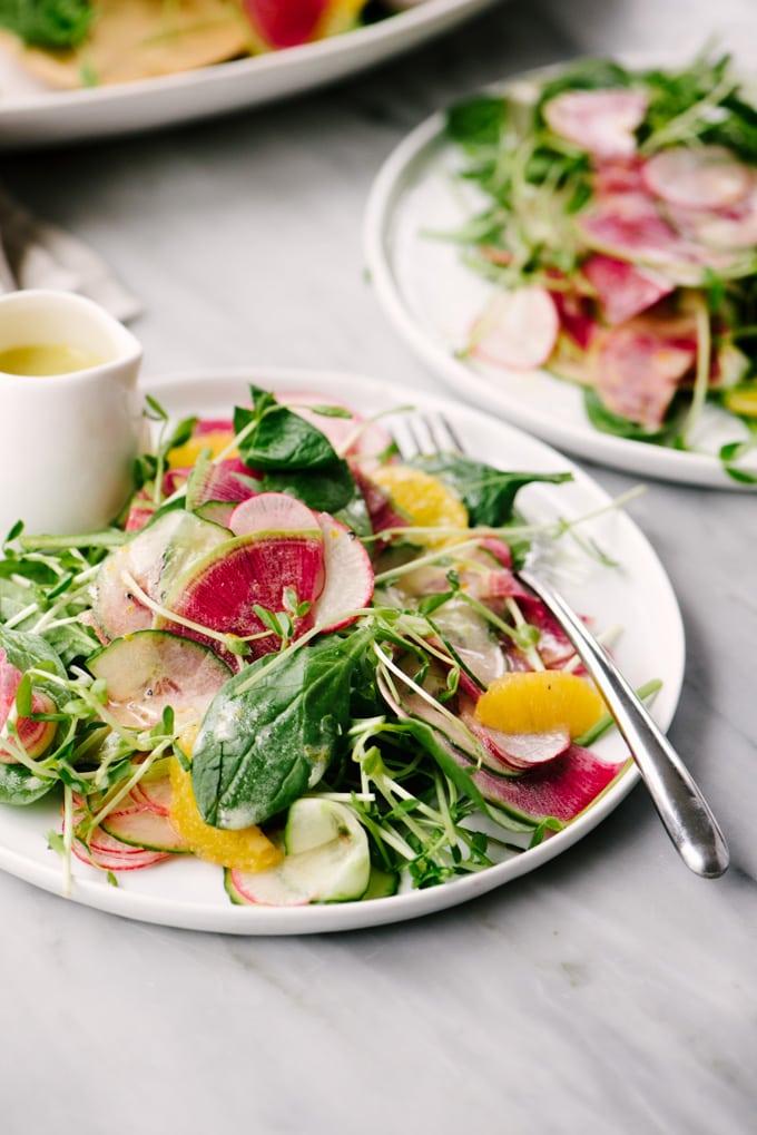 Two plates of radish salad with meyer lemon vinaigrette on a marble table.