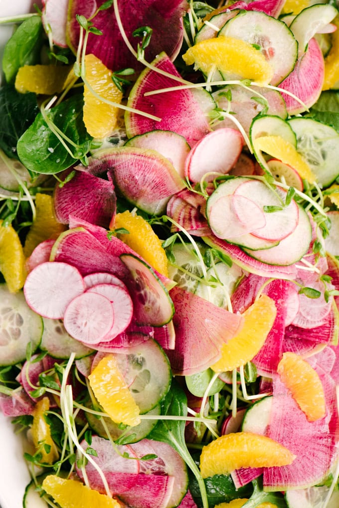 A macro image of a platter of radish salad with three types of thinly sliced radishes, cucumber, pea shoots, baby spinach, and citrus supremes.