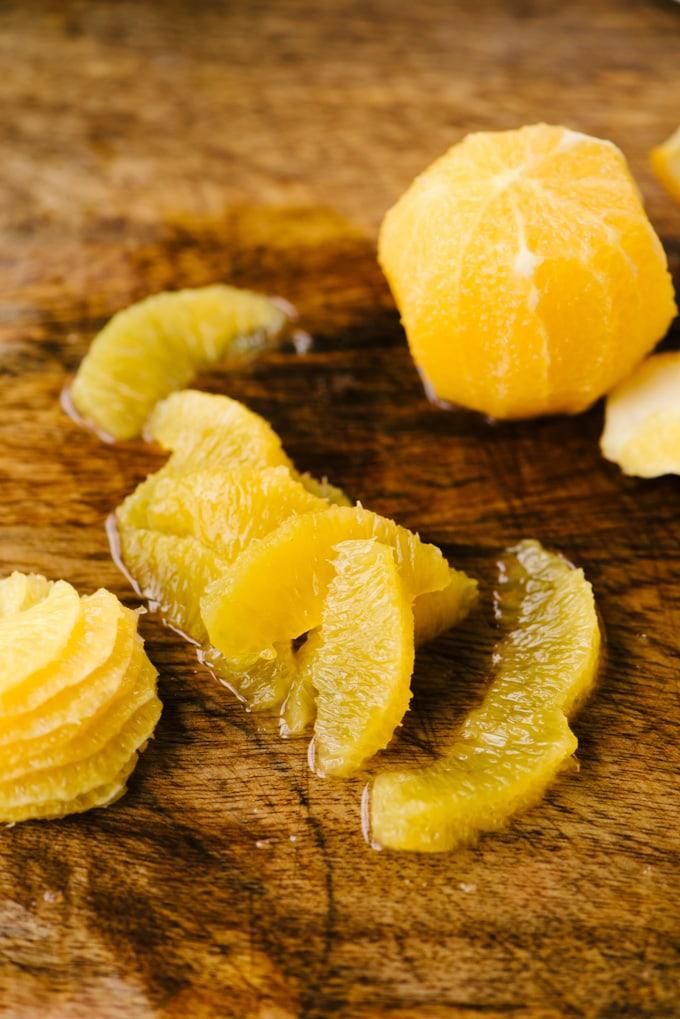 An orange sliced into supremes on a wood background for garnishing a radish salad.
