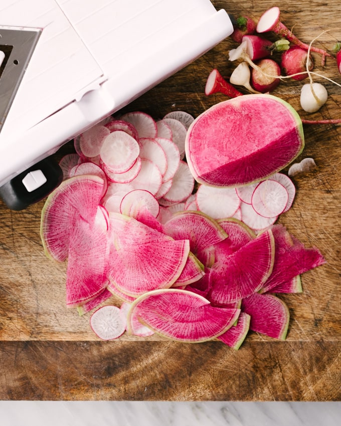 How to make a radish salad with meyer lemon vinaigrette. Thinly sliced radishes next to a madonline vegetable slices on a wooden cutting board.