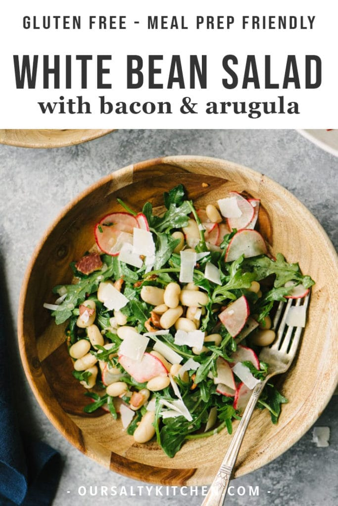 Gluten free and grain free white bean salad with bacon, radishes, fresh herbs, and arugula in a wooden bowl on a cement background.
