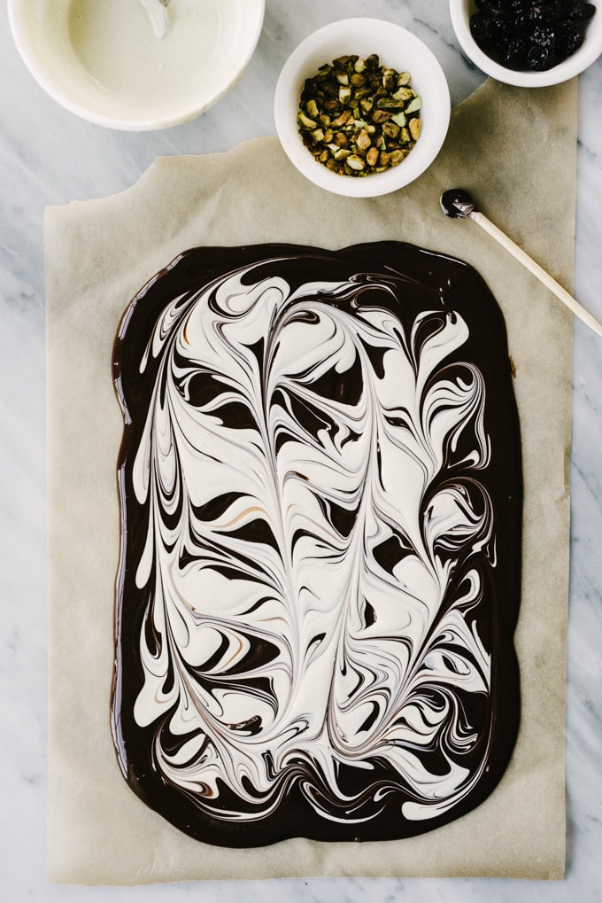 White and dark chocolate swirled together on a piece of parchment paper ready to be sprinkled with toppings.