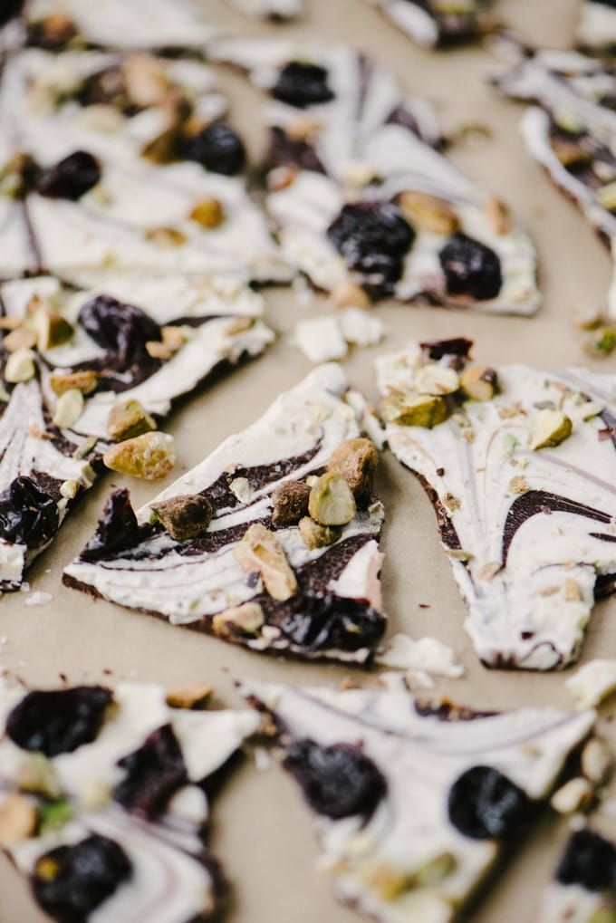 White and dark chocolate swirled bark with pistachios and dried cherries on a piece of parchment paper.