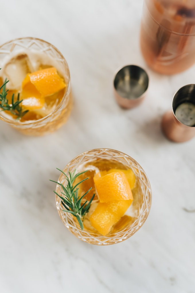 Two rosemary bourbon cocktails on a marble table - a sweet winter bourbon cocktail recipe.