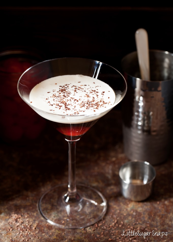 A black forest cocktail in a martini glass garnished with chocolate, made with bourbon.