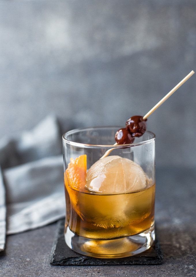 A winter bourbon cocktail recipe made with smoked ice in a rocks glass on a grey table.
