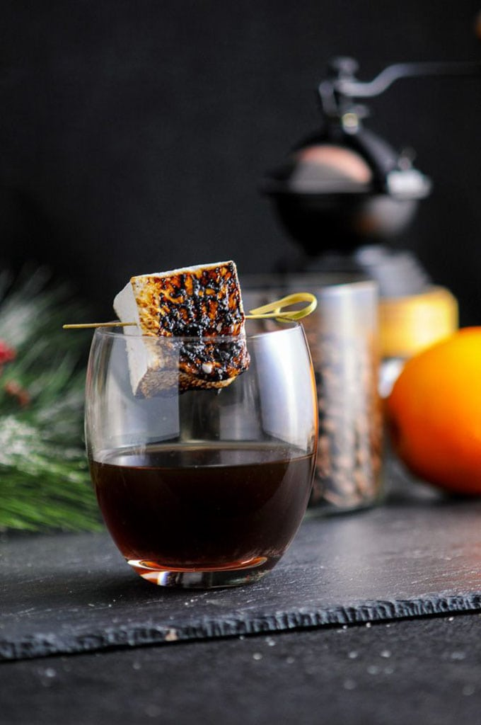 A bourbon and coffee cocktail with a roasted marshmallow on a black table.