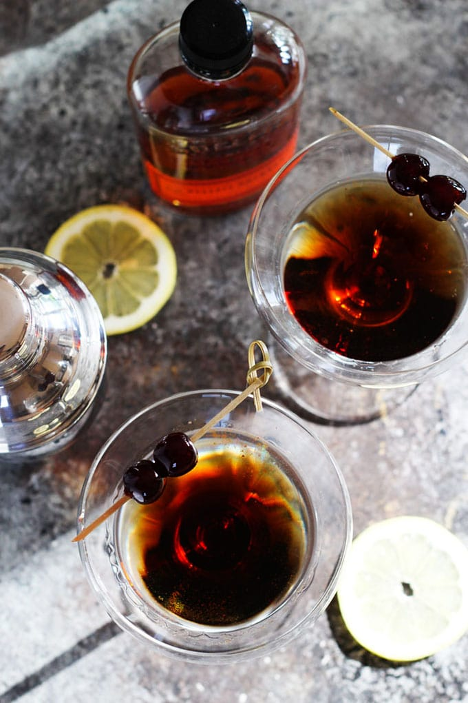 Two martini glasses with a Sweeney Todd cocktail - a cozy winter bourbon cocktail recipe.