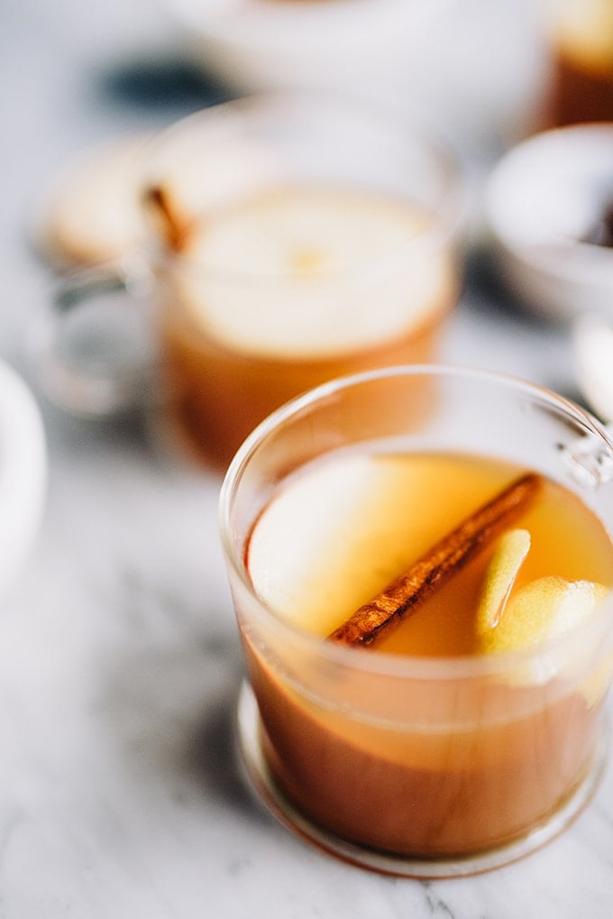 Two glass mugs filled with an apple cider hot toddy and garnished with apple and cinnamon sticks - a warm and comforting winter bourbon cocktail recipe.