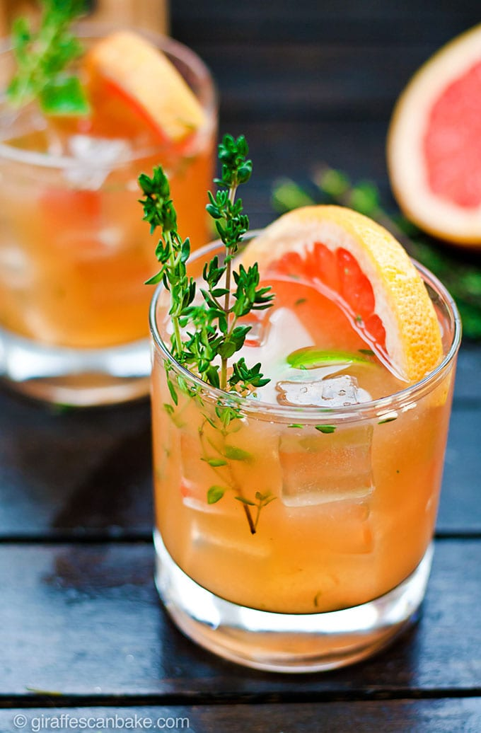 Two glasses of grapefruit and thyme bourbon smash - a bright and refreshing winter bourbon cocktail recipe.