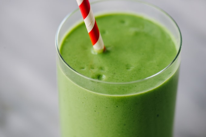 A detail shot of my favorite protein packed mango spinach smoothie in a glass with a red and white straw on a marble background.