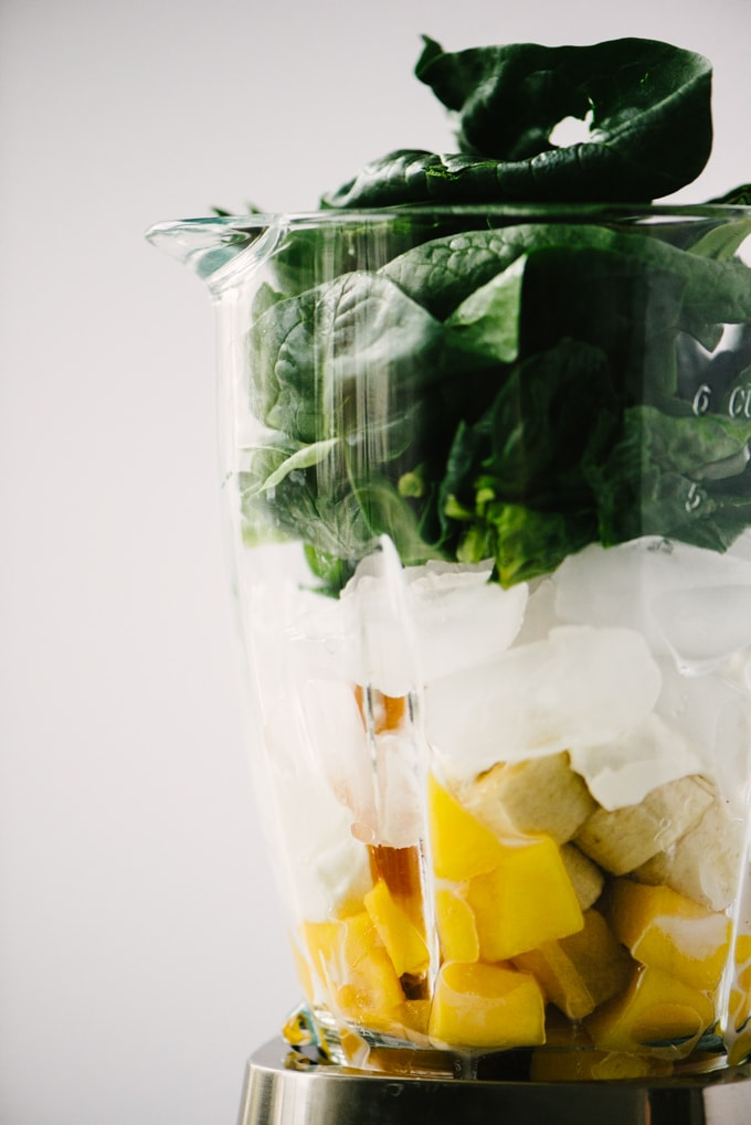 How to make my favorite mango spinach smoothie! A blender filled with diced mango, sliced banana, honey, yogurt, ice, and spinach.