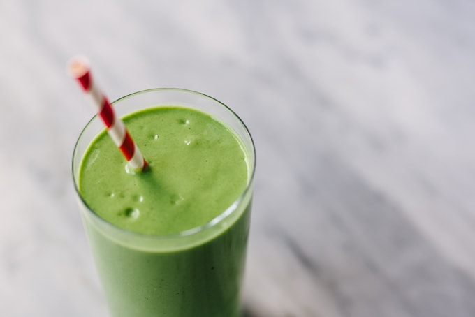A close-up image of my favorite mango spinach smoothie in a glass with a red and white straw on a marble background.