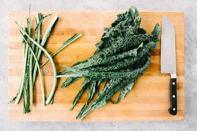 How to make kale and brussels sprout salad. Stemmed lacinato kale leaves on a wooden cutting board.