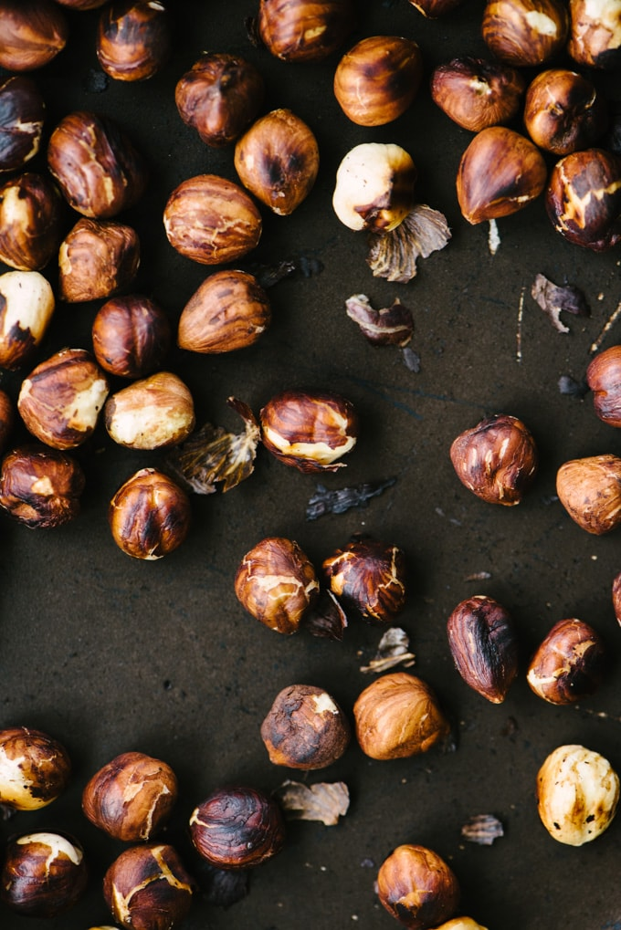 A close-up image of whole toasted hazelnuts in a saute pan.