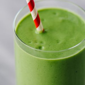 Mango spinach green smoothie in a glass with a red and white striped straw.