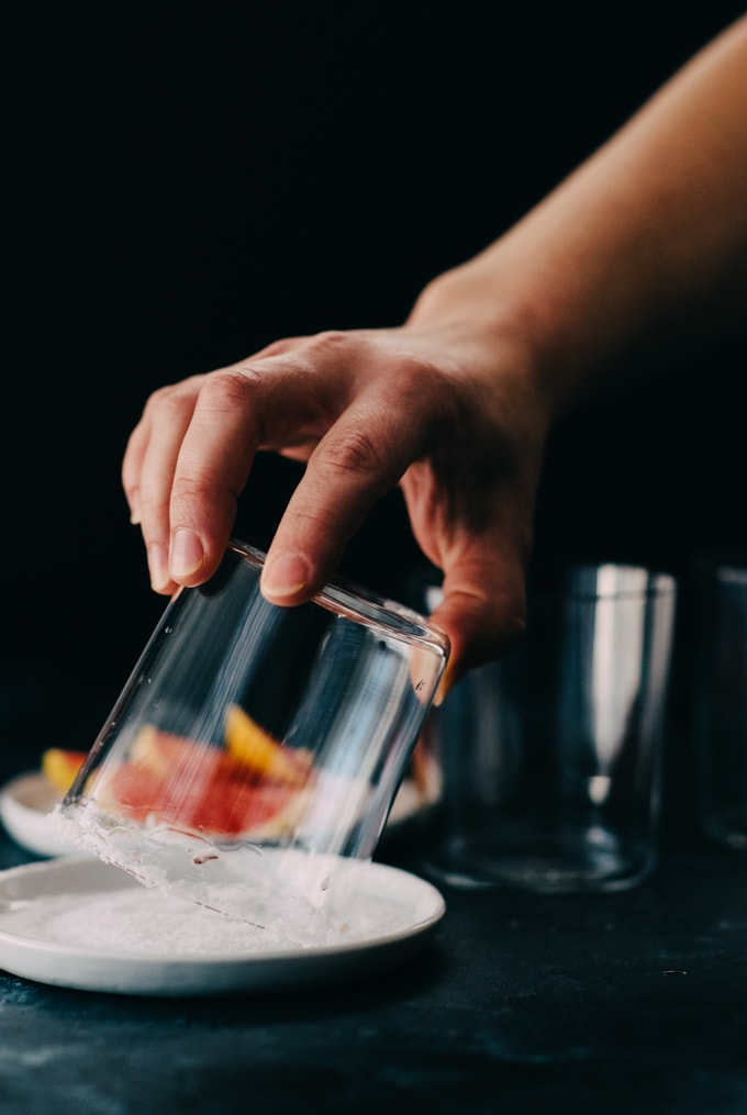 Dipping the rim of a rocks glass into salt to make a salted rim for a paloma.