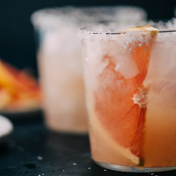 Paloma cocktail made with fresh grapefruit juice in a cocktail glass with a grapefruit slice and sugared rim.