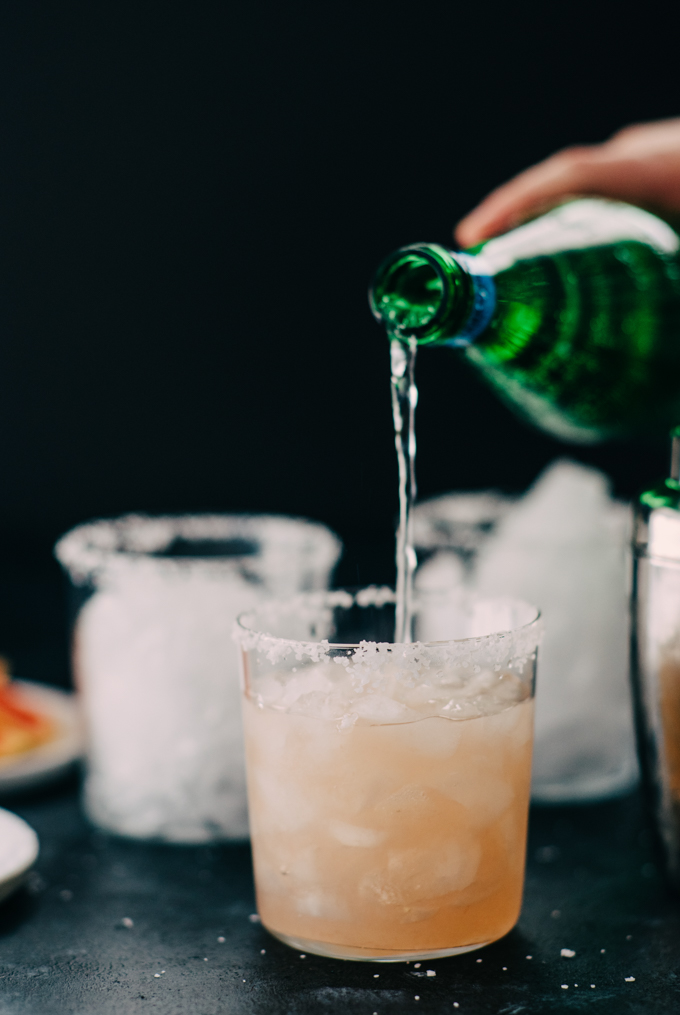 Topping off a paloma cocktail with soda water.