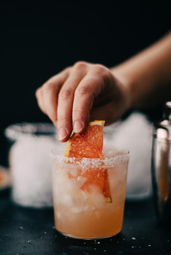 Placing a grapefruit slice into a paloma cocktail.