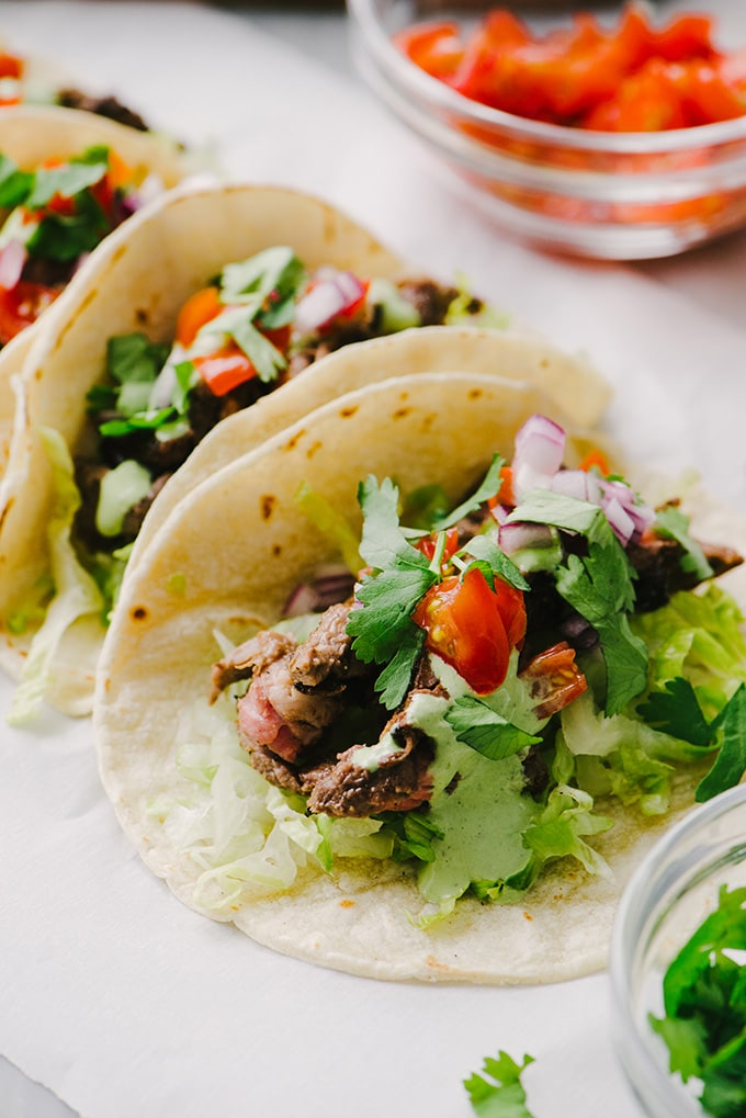 Grilled skirt steak tacos with homemade cilantro sour cream, tomatoes, and red onion.
