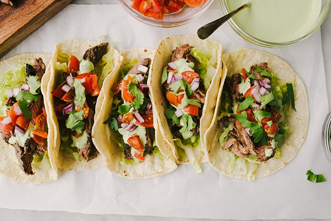 Skirt steak tacos with homemade marinated grilled to medium rare in corn tortilla shells.