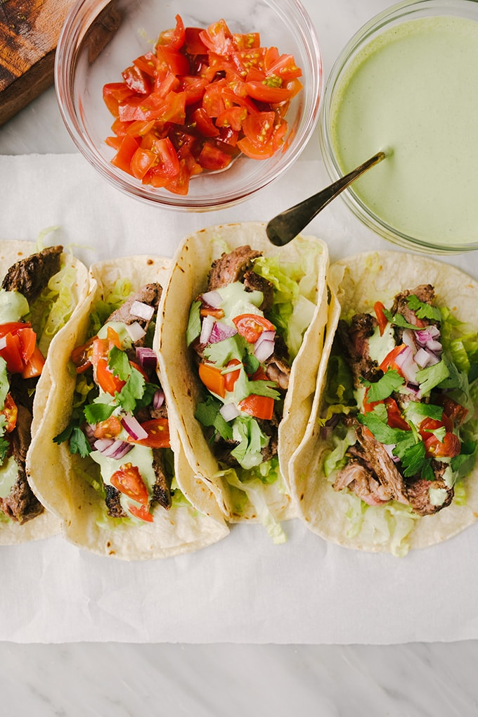 Four grilled skirt steak tacos with cilantro lime sour cream, diced tomatoes, red onion, and cilantro.