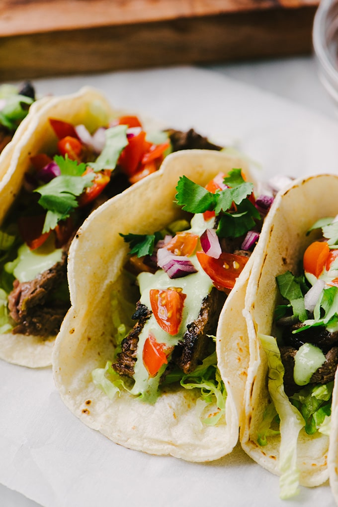 Grilled skirt steak tacos topped with cilantro lime crema on parchment paper.