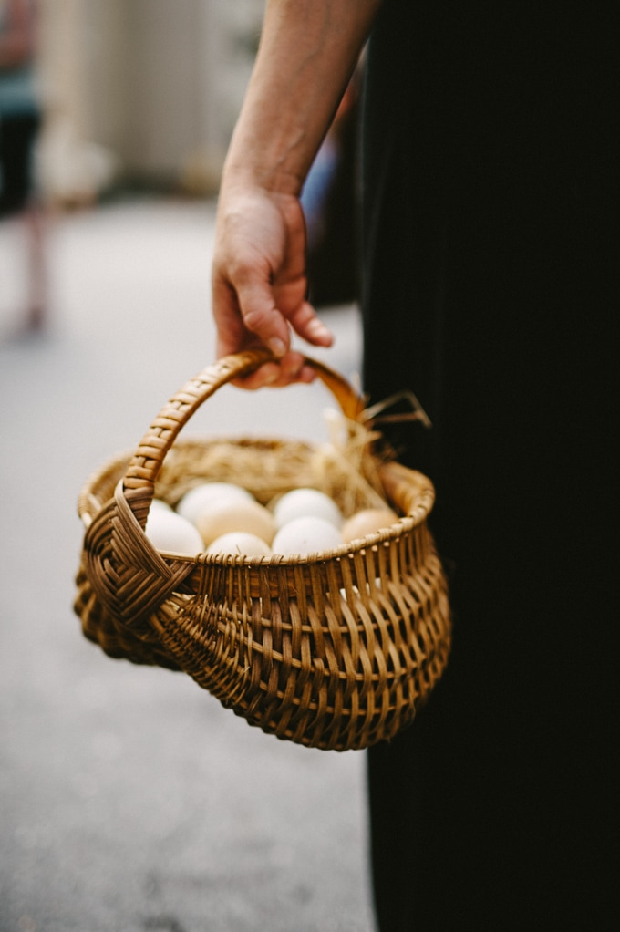 A woman holding a basket of pastured farm fresh eggs. Eat local without breaking the bank by focusing on budget items, like eggs, first!