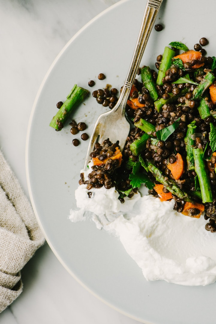 Cooked black lentils with roasted carrots on a plate with a dollop of greek yogurt.